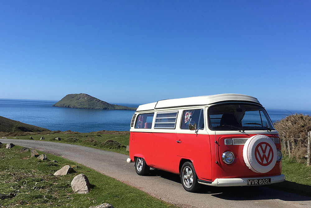 Our red campervan Poppy with view of Bardsey island